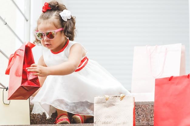 Mała dziewczynka w okularach przeciwsłonecznych siedzi na schodach w centrum handlowym z kolorowymi torbami