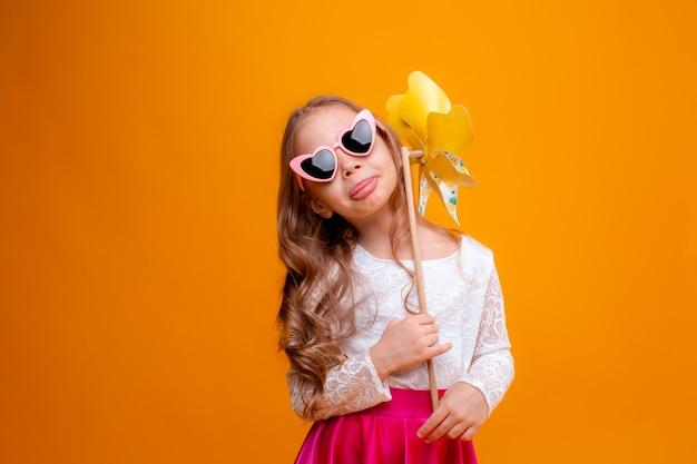 Mała dziewczynka w okularach przeciwsłonecznych trzyma zabawkę wiatraczek na żółtym tle