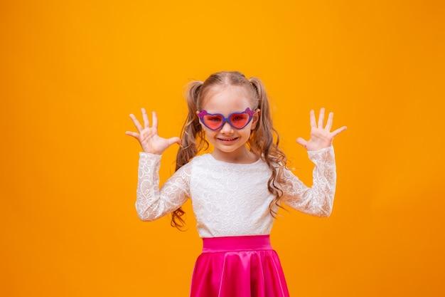 Mała dziewczynka w okularach przeciwsłonecznych uśmiecha się na żółtym tle