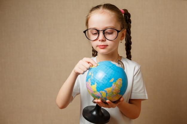 Mała dziewczynka w okularach szuka miejsca na kuli ziemskiej.