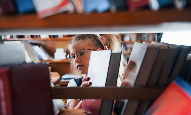 Mała dziewczynka w okularach szukająca książki w bibliotece