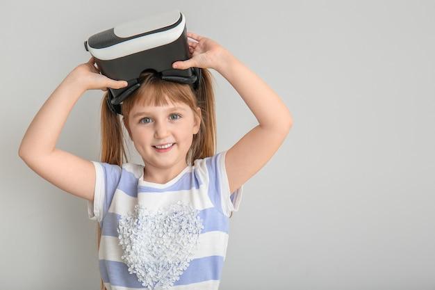Mała dziewczynka w okularach wirtualnej rzeczywistości na świetle
