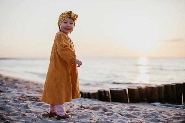 Mała dziewczynka w orientalnych strojach spacerująca po plaży o zachodzie słońca