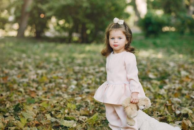 Mała dziewczynka w parku w różowym smokingowym bawić się