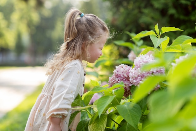 Mała dziewczynka w parku wącha krzak, nad którym pochyla się kwiat