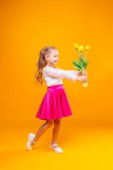 Mała dziewczynka w pełnym wzroście trzyma bukiet tulipanów na żółtym tle