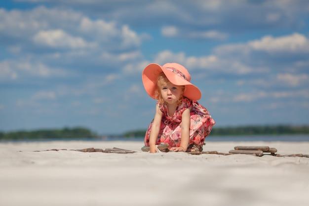 Mała dziewczynka w pięknej sarafnie bawi się w piasku na plaży.