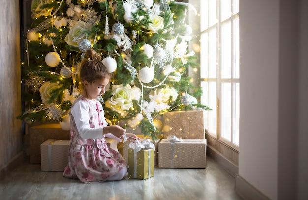 Mała dziewczynka w pięknej sukience siedzi pod choinką z pudełkiem i kokardą. światło z dużego okna, ciemny pokój, domowy komfort, boże narodzenie, magia i radość. nowy rok, biały wystrój