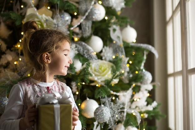 Mała dziewczynka w pięknej sukni siedzi pod choinką z pudełkiem i kokardą. światło z dużego okna, ciemny pokój, domowy komfort, boże narodzenie, magia i radość.