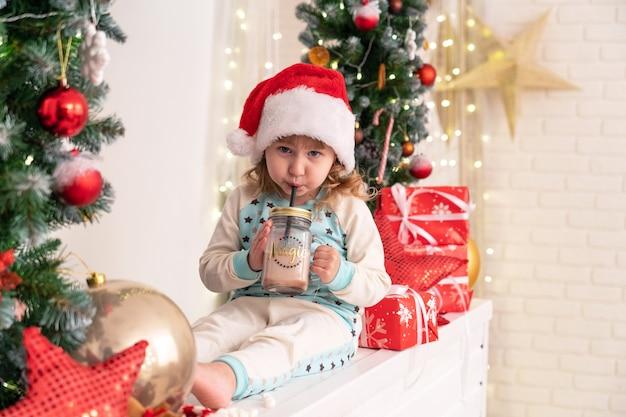Mała dziewczynka w piżamie i czapce mikołaja pije mleko kakaowe! otacza świąteczna atmosfera.