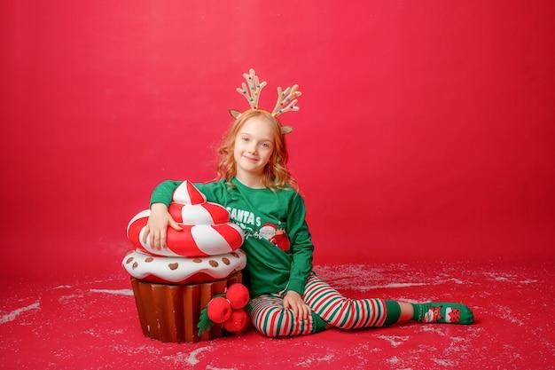 Mała dziewczynka w piżamie na czerwonym tle z prezentami