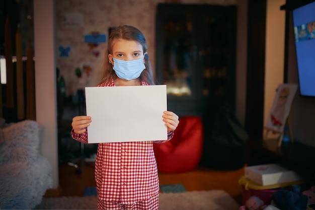Mała dziewczynka w piżamie z maską ochronną trzyma puste prześcieradło