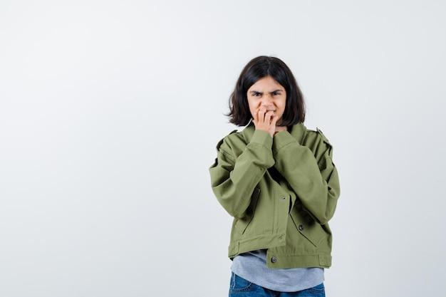 Mała dziewczynka w płaszczu, koszulce, dżinsach obgryzających paznokcie i ponurym, widok z przodu.
