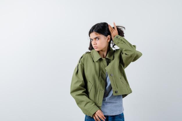 Mała dziewczynka w płaszczu, koszulce, dżinsach pozowanie podczas układania jej słyszeć i wyglądać ładnie, widok z przodu.