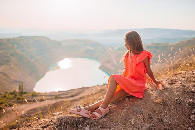 Mała dziewczynka w pobliżu jeziora w ciągu dnia z niesamowitym krajobrazem
