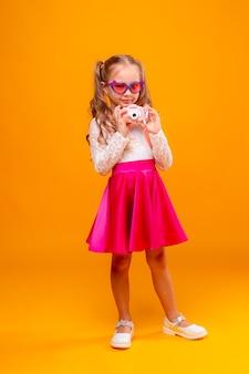 Mała dziewczynka w podróży zawiera aparat na żółtym tle
