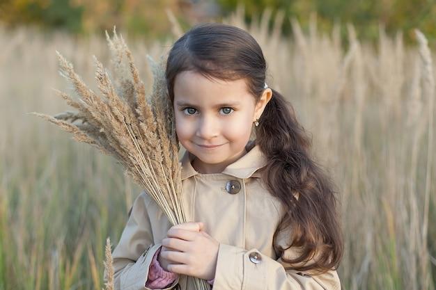Mała dziewczynka w polu trzyma bukiet pszenicy.