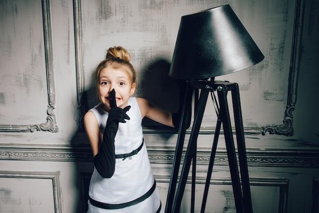 Mała dziewczynka w rocznik sukni. dziecko w eleganckiej efektownej sukni i rękawiczkach. retro dziewczyna, modelka, uroda, lampa podłogowa. retro, fryzjer, makijaż, pin up. moda w stylu pinup.
