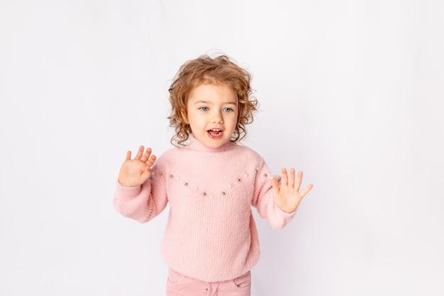 Mała dziewczynka w różowe zimowe ubrania na białym tle raduje się, miejsce na tekst