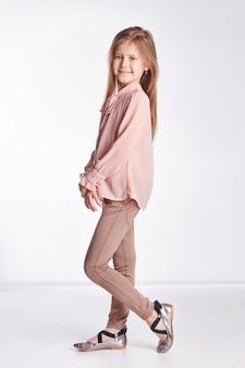 Mała dziewczynka w różowej bluzce i spodniach pozuje