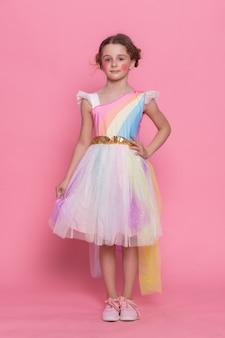 Mała dziewczynka w różowej sukience i kapeluszu urodzinowym siedzi na podłodze z wielu obecnych pudełko, balony w domu serpentyny urodzinowe, wszystkiego najlepszego. świętujemy