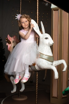 Mała dziewczynka w różowej sukience i koronie na karuzeli z białym zającem.
