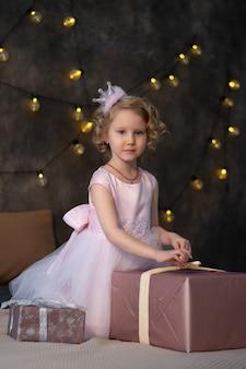 Mała dziewczynka w różowej sukience i koronie na łóżku z prezentami.