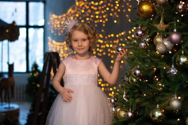 Mała dziewczynka w różowej sukience i koronie obok choinki z prezentami.