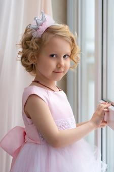 Mała dziewczynka w różowej sukience i koronie uśmiecha się przy oknie.