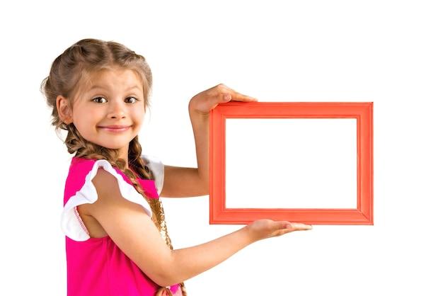 Mała dziewczynka w różowej sukience trzyma ramkę na zdjęcia.