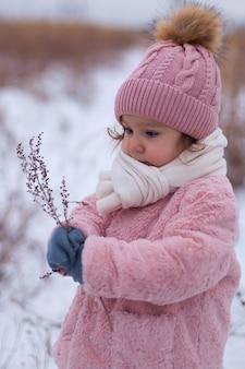 Mała dziewczynka w różowym futrze bawi się na dworze otoczona śniegiem. okres zimowy, pojęcie zdrowej aktywności dzieci