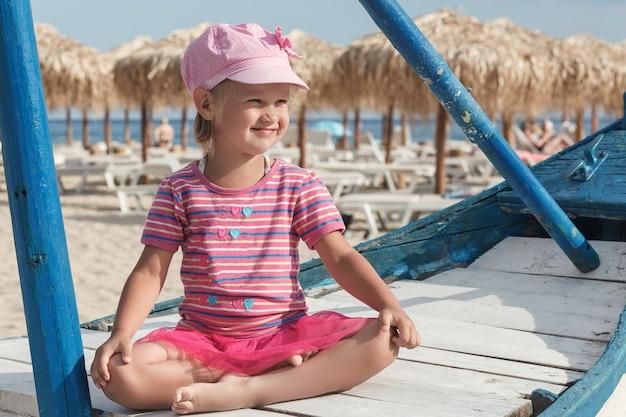 Mała dziewczynka w różowym siedzeniu w pozycji lotosu na niebieskiej łódce na plaży
