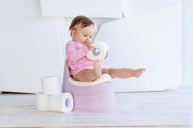 Mała dziewczynka w różowym ubraniu siedzi na nocniku w jasnym pokoju i bawi się papierem toaletowym