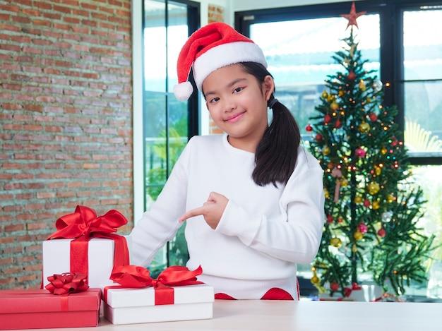 Mała dziewczynka w santa hat z pudełkami w domu.