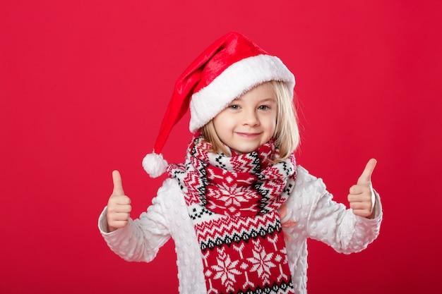 Mała dziewczynka w santa kapeluszu i szaliku na czerwieni
