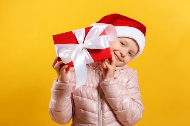 Mała dziewczynka w santa kapeluszu trzyma boże narodzenie prezent.