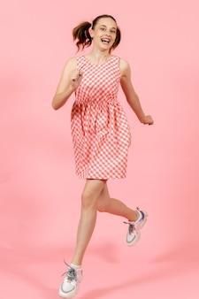 Mała dziewczynka w ślicznej jasnej sukience skacząc szczęśliwie na różowo
