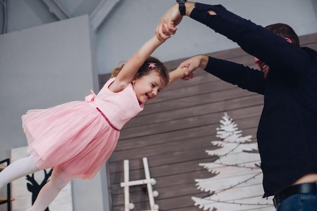 Mała dziewczynka w ślicznej różowej sukience świetnie się bawi z ojcem w świątecznej atmosferze.