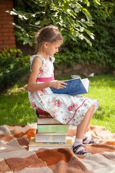 Mała dziewczynka w ślicznej sukience siedzi na stosie książek i czyta
