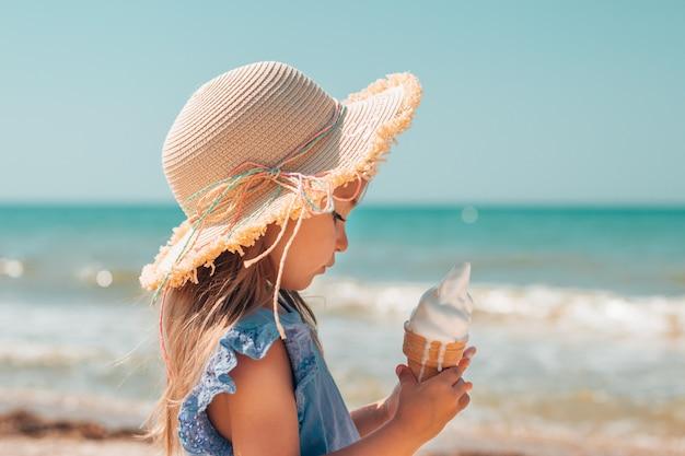 Mała dziewczynka w słomkowym kapeluszu jedząca lody z miękkiego stopionego masła w szklance gofrów nad morzem
