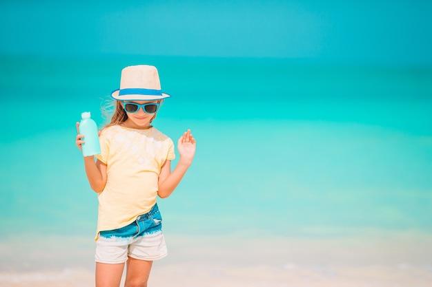 Mała dziewczynka w słomkowym kapeluszu na plaży z butelką kremu przeciwsłonecznego. ochrona przed słońcem