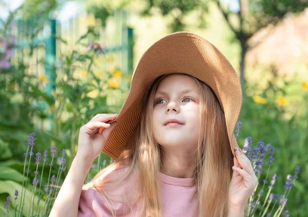 Mała dziewczynka w słomkowym kapeluszu otoczona lawendowymi kwiatami