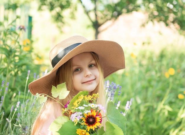Mała dziewczynka w słomkowym kapeluszu w otoczeniu kwiatów lawendy. portret szczęśliwa mała dziewczynka blondynka z długimi włosami w lawendowym polu