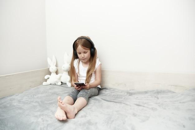 Mała dziewczynka w słuchawkach, słuchanie muzyki