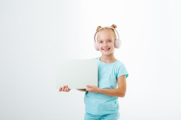 Mała dziewczynka w słuchawkach trzyma białą kartkę papieru na białym tle na białym tle