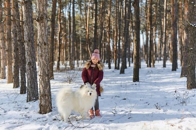 Mała dziewczynka w śnieżnym zimowym lesie bawi się białym psem samojeda