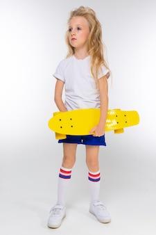 Mała dziewczynka w sportowych spodenkach z deskorolką w ręku