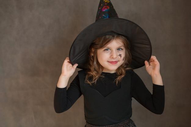 Mała dziewczynka w stroju czarownicy halloween z siecią i spyder na twarzy