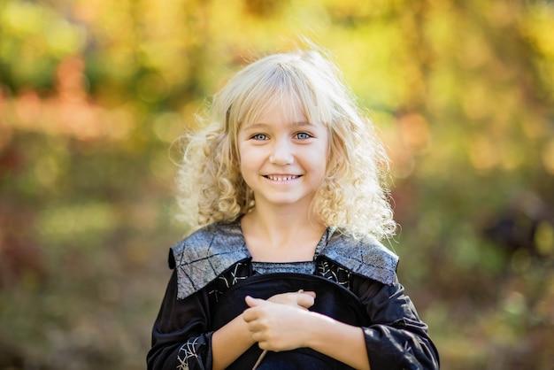 Mała dziewczynka w stroju czarownicy świętuje halloween na zewnątrz i baw się dobrze.