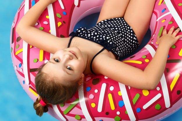 Mała dziewczynka w stroju kąpielowym leży na nadmuchiwanym kole.